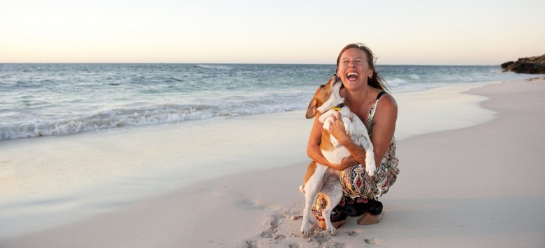 Happy looking mature woman is enjoying a sunset at the beach with her pet dog, with ocean and twilight sky as background and copy space.
