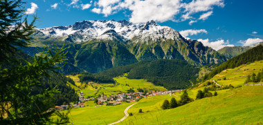 """Green mountain landscape with a bit of snow on the mountain tops near Nauders, Austria."""