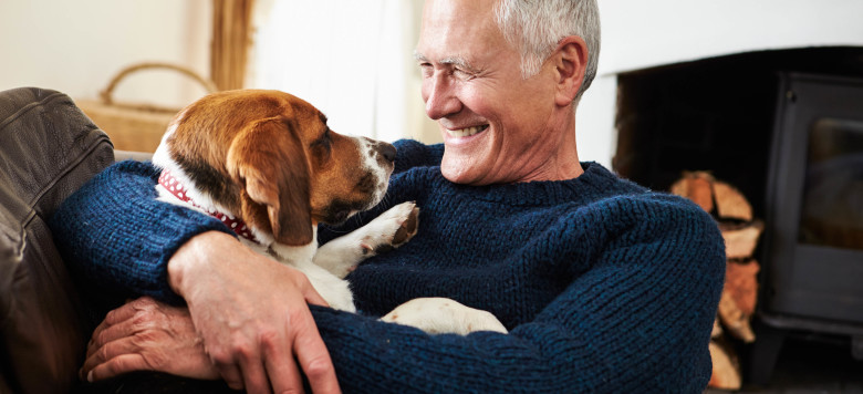 Senior Man Relaxing At Home With Pet Dog Smiling